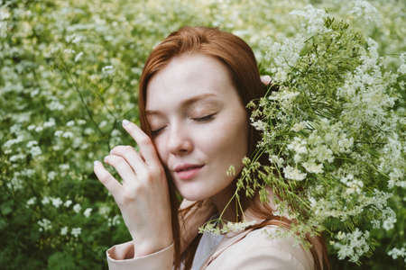 Mental Health Awareness Month, behavioral health care. Post COVID-19 pandemic mental health challenges. Red-haired young woman on green nature trees and flowers background 免版税图像 - 168508710