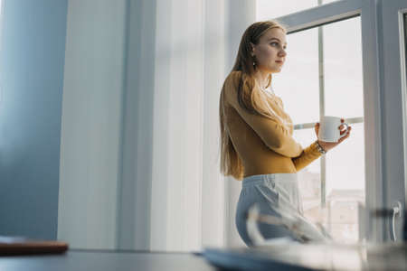 Worker burnout, Emotional burnout, Mental health problem. Tired businesswoman, worker standing by the window in office on desktop with a computer background. Long working day in the office