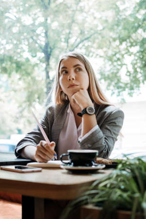Thoughtful young woman, student girl think at workplace at cafe. Professional content creator thinking about project, student search new idea inspiration in office cafe 免版税图像