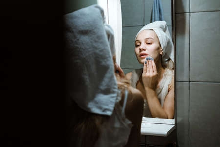 Use Wash Off Face Mask, Using Peel-Off Mask Correctly. Young woman in towel on her head wash face after removing mask in bathroom. 免版税图像 - 168508742
