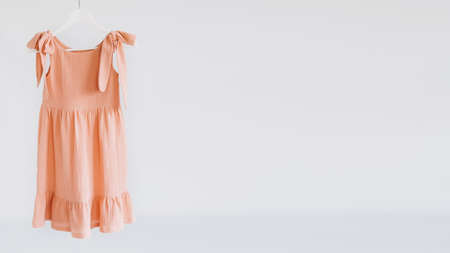 Muslin Eco Friendly Clothing, Organic Cotton Muslin Clothes. Natural tones dresses hanging on a hanger on white background