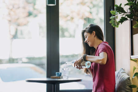 Drinking more water, drink water reminder, keep water tracker. Brunette girl drinking water from a glass sitting in cafe by the window.