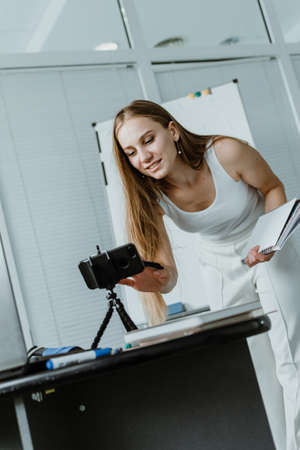 Gig economy, Side hustle, earn extra, money making, side job, side money, second job, hustling, hustle gig concept. Young woman speaking in front of camera cell phone