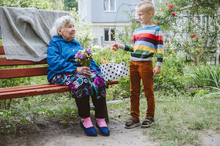 90 year old great-grandmother, grandmother with grandson together. Grandson hugs his beloved grandmother. Kid grandson came to grandmother with flower bouquet and food basket