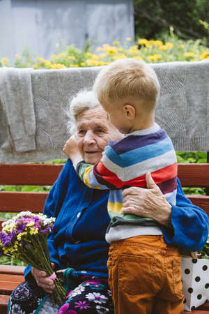 90 year old great-grandmother, grandmother with grandson together. Grandson hugs his beloved grandmother. Kid grandson came to grandmother with flower bouquet and food basket 免版税图像 - 168508808