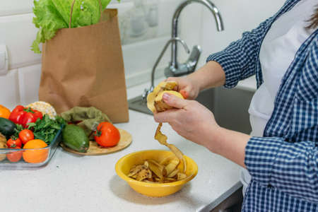 Food Loss and Food Waste. Reducing Wasted Food At Home. Solving the problem of Food waste. Female hands peeling potatoes, potato peel in a bowl