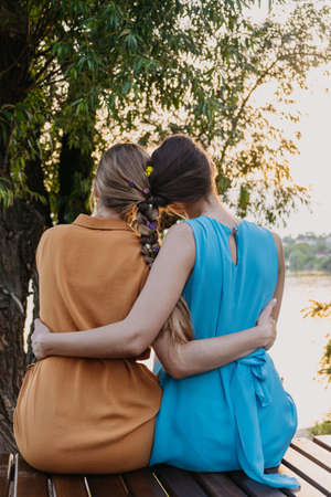 Female friendship femininity, diverse, support, partnership, girlfriend concept. Two girls blonde, brunette, with braided plait sitting and hugging in the nature sunset background