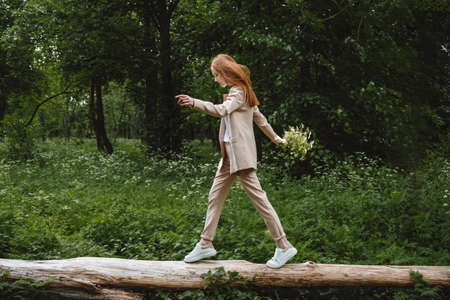 Stress and resilience. Spend Time in Nature to Reduce Stress and Anxiety. Nature break relieves stress. Young woman in suit enjoying nature and walking in green summer park