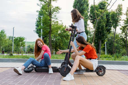 Three Young girl friends on vacation having fun driving electric scooter through the city park. Ecological and urban city transport, summer leisure activities concept 免版税图像