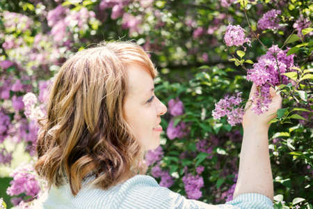 Candid authentic portrait of 30s 40s caucasian blonde woman with lilac flowers. 30 40 year old woman enjoying life in lilac flowers nature background. Reinvention, Life Changes, reinvent yourself 免版税图像