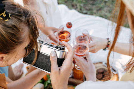 Social Media Content Ideas, Content creator for brands, food blog, summer picnic. Young woman food blogger, content creator with professional camera taking food photo of croissant in picnic on nature