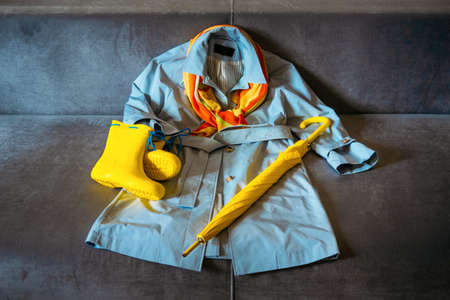 Rainy Mood, outfit for rainy day. Blue raincoat, yellow rubber boots and umbrella on a gray sofa. Colors of the year Ultimate Gray and Illuminating yellow background 免版税图像