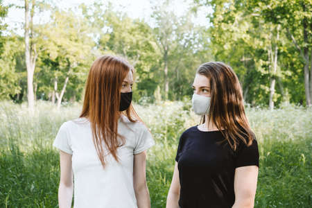 Two red-haired and brown-haired girlfriends in black and white face mask on nature background. Friendship, Symmetry, alternative, contrast black and white portrait of two girls in face masks
