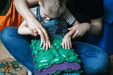 Sensory Play for Kids with Special Needs. Activities for kids with disabilities, Cerebral Palsy. Boy with Cerebral Palsy playing with Sensory Mat Massage Game Puzzle Mats for Kids Banque d'images