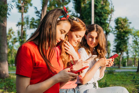 Three girl friends watching mobile smart phones and having fun sitting on bench in public park.