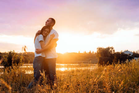 Couple in love silhouette on nature sunset yellow and purple sky background. Young couple enjoying the sunset in the meadow. Stock Photo