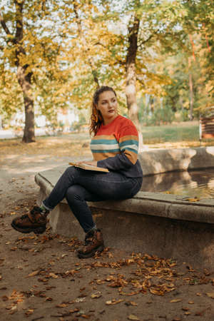 Young plus size woman reading book in fall autumn park in sun lights.