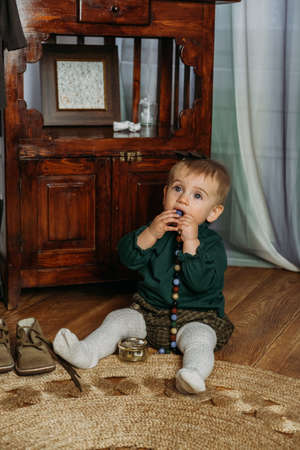Gender-neutral baby fashion. Unisex kid clothes. Little toddler girl in green and brown longsleeve and shorts. Selective focus