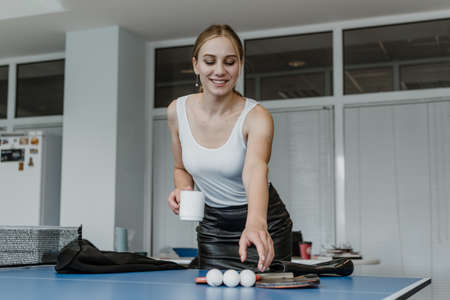 Meal and Rest Breaks, Break in office work. Time for relaxation and rest at workplace. Young business woman, company employee taking break, drinking coffee and playing table tennis Stock Photo