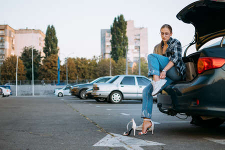 Driving Shoes For Car Enthusiasts. Driving Shoes for Woman To Wear on the Road. Woman changes high heels shoes in comfortable sneakers before driving, sitting in car Stock Photo