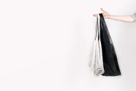 Canvas cotton shopping eco friendly bag vs plastic shopping bag in female hand on white background. Zero waste, plastic free, no plastic concept Stock Photo