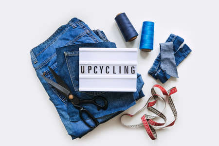 Denim Upcycling Ideas, Using Old Jeans, Repurposing Jeans, Reusing Old Jeans, Upcycle Stuff. Lightbox with text Upcycling, Stack of old blue jeans, scissors, thread and sewing tools in sewing studio. Stock Photo