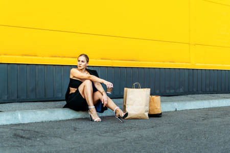 Shopping, sale, Young stylish blonde woman with shopping bags resting after shopping. Fashionista Woman with shopping bags on outdoor parking. Stock Photo