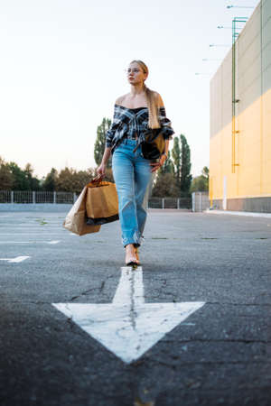 Shopping, sale, Happy young stylish blonde woman with shopping bags go to car in parking on white arrow after shopping. Woman with shopping bags on outdoor parking. Stock Photo