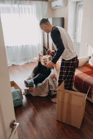 Moving day, Move Into New Home. Young happy couple, newlyweds family having fun in room with carton boxes with clothes and other things prepared for moving in or moving out of home