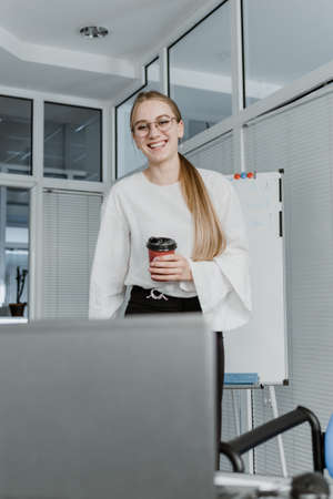 Remote Meetings, Video Conferencing. Young business woman drinking coffee and communicating with colleagues via video call on laptop in the office Stock Photo