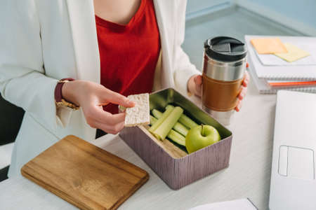 Female hands holding lunch zero waste box, food delivery box with healthy meal weight loss diet menu, vegan food at workplace in office. Office employee having vegan lunch at workplace