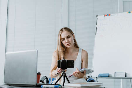 Young woman have online meeting, online courses, remote coaching, near open laptop and smartphone camera. Blog post, vlog, online course, remote webinar recording