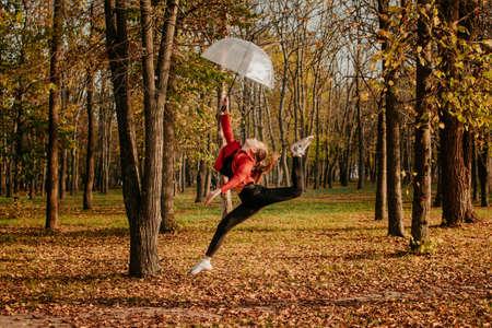 Hello fall, autumn season, fall mood, positive emotions. Teenager girl jumping with transparent umbrella and enjoying life in autumn sunny park Stock Photo