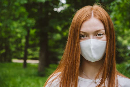 Face Mask Rules Return. Outdoor portrait of redhead Woman with protective white mask on green trees backgroung. Young woman in protective facial mask over green background Stock Photo