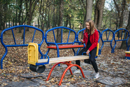 Gen z, generation z, Zoomers device addiction, digital detox. Teenager girl alone rides on a swing in an autumn park with smartphone in her hands.