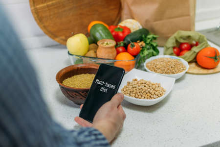 Whole-food, plant-based diet for boost health. Female hand cell phone with Plant-Based Menu recipes and healthy meal, vegetables, fruits, whole grains, healthy protein, oils. Vegan, vegetarian diet Stock Photo