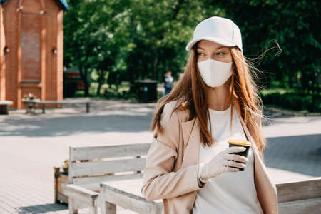 Food and drink businesses during coronavirus pandemic. Coffee to go takeaway cup in female hands in gloves. Restaurants, pubs, bars, nightclubs and takeaway services working safely during coronavirus