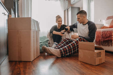 Moving day celebration. Yong couple Move Into New Home. Young happy couple, newlyweds family drinking wine and having fun in room with carton boxes in new home