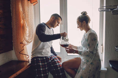Young couple drinking coffee in kitchen at home in the morning. Young happy couple, newlyweds family start new day and have morning coffee together