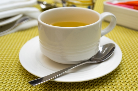 White cup of green tea on white saucer with a spoon