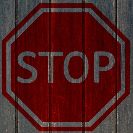 GRUNGE STOP SIGN ON DARK WOODEN PLANK Stock Photo