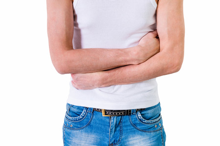 Man in white undershirt holding hands on his stomach  isolated on white background. photo
