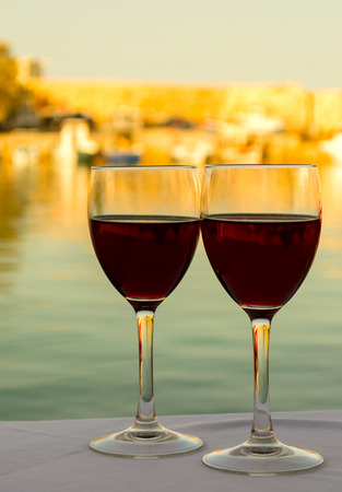 Two glasses of re wine on the table opposite sea sunset background photo