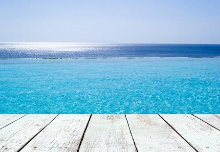 paisaje mediterraneo: Piscina de desbordamiento con vistas sobre el Mar Egeo, Creta, Grecia y tablón de madera vacía en perspectiva Foto de archivo
