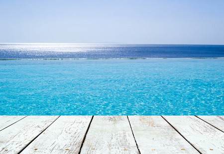 Infinity swimming pool with a view on Aegean Sea, Crete, Greece and empty wooden plank in perspective