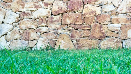 Old stone wall and green grass photo