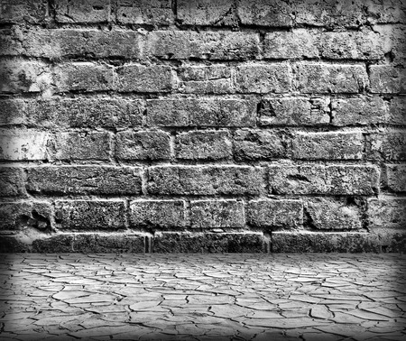 Grungy textured brick wall with cracked ground in old neglected interior photo
