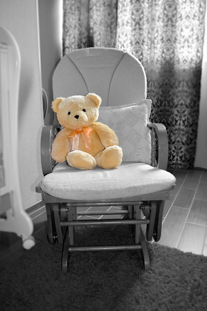 Teddy bear in rocking chair in childrens room interior photo