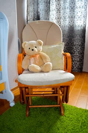 Teddy bear in rocking chair in children room interior  Vector