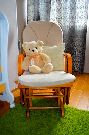 children room: Teddy bear in rocking chair in children room interior